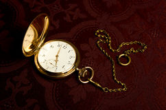 Gold pocket watch on maroon cloth. Gold pocket watch on on maroon cloth close-up Stock Images