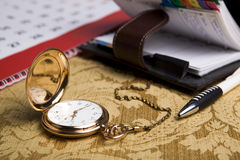 Gold pocket watch and a wall calendar and sketchpad. Gold pocket watch with wall calendar and sketchpad, pen close-up Stock Image