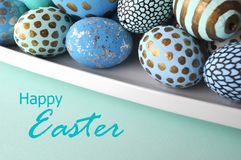 Gold polka dots, glitter and stripes on blue and teal decorated Easter eggs on solid pastel color background