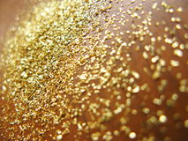 Gold powder. Closeup over wooden surface Royalty Free Stock Images