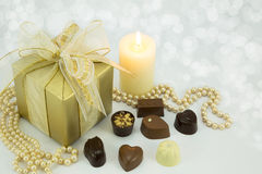 Gold present with assorted chocolates. Gold chocolate box with ribbon and assorted chocolates Stock Image