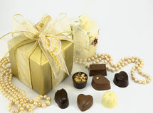 Gold present with assorted chocolates. Gold chocolate box with ribbon and assorted chocolates Royalty Free Stock Photo