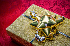 A Gold Present Gift Box with Bow on Red Stock Photography