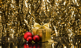 Gold present and Christmas tree baubles Royalty Free Stock Image