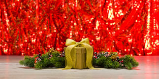 Gold present and Christmas tree branches Royalty Free Stock Images