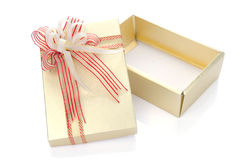 Gold present gift box with overwhelming bow isolated on white Stock Photography