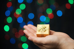 Gold present on hand of woman have bokeh as background Stock Photos