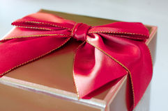 Gold present with red bow - Stock Photo