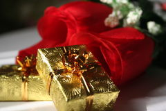 Gold presents. Gold preseents and silk flowers stock photo