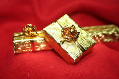 Gold presents. On red cover Royalty Free Stock Photography