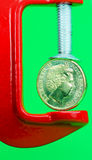 Gold Pressure. A gold coin held in a red clamp with a light pastel green background, indicating the pressure is on currency during these uncertain times Royalty Free Stock Photos