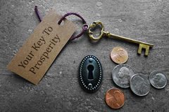 Gold prosperity key. Coins with gold key and Prosperity tag Stock Photos