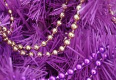 Gold and purple bead garlands strung on an artificial Magenta colored tree Royalty Free Stock Images