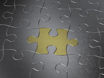 Gold puzzle piece. In a chrome jigsaw puzzle Royalty Free Stock Image