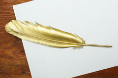 Gold quill pen. On a white paper and wooden table Royalty Free Stock Photography