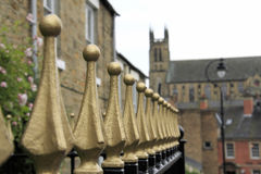 Gold Railings at Durham. Ornate cast iron railings painted Gold and black in a street in Durham City, County Durham, England. In the background is St Bede's Royalty Free Stock Photo