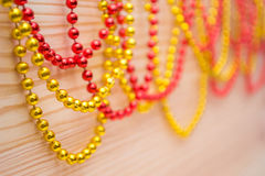 Gold and red beads on a wooden board. Pine boards. Wooden background. Stock Photography