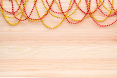 Gold and red beads on a wooden board. Wooden background with beads. Stock Images