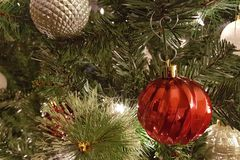 Gold and red Christmas ball decorations. Hanging from a Christmas tree with lights stock photo