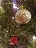 Gold and red Christmas ball decorations. Hanging from a Christmas tree with lights royalty free stock photos