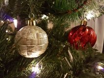 Gold and red Christmas ball decorations. Hanging from a Christmas tree with lights royalty free stock images