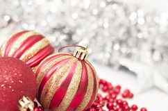 Gold & Red Christmas Baubles. With tinsel in the background Stock Image