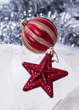 Gold & Red Christmas Baubles. With tinsel in the background Stock Photos