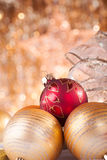 Gold and red christmas baubles. On background of defocused golden lights Royalty Free Stock Image