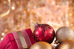 Gold and red christmas baubles and red box. On background of defocused golden lights Stock Photo