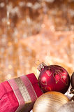 Gold and red christmas baubles and red box. On background of defocused golden lights Stock Photography