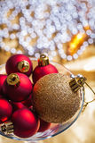 Gold and red christmas baubles in wineglass very close up Royalty Free Stock Image