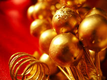 Gold and Red Decoration. Golden holiday ornaments on a red background Royalty Free Stock Photo