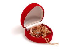 Gold in a red gift box. On white Royalty Free Stock Image