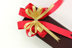 Gold and red ribbon bow with giftbox on white background Royalty Free Stock Images
