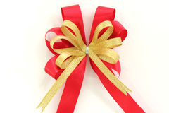 Gold and red ribbon bow on white background Stock Image