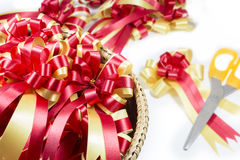 Gold and red ribbons with scissors bow on white background Stock Image