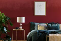 Gold and red sophisticated bedroom. Gold lamp on table next to bed with green bedding in sophisticated red bedroom interior with poster Royalty Free Stock Image