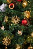 Gold, red and straw vintage decorations in the Scandinavian style on an artificial Christmas tree. Close-up stock images