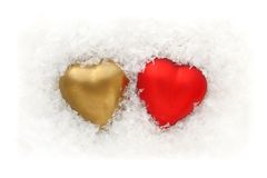 Gold and red two hearts in the snow. On a white background Stock Photography