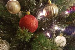 Gold and red and white Christmas ball decorations. Hanging from a Christmas tree with lights royalty free stock photo