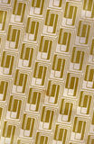 Gold Repeating Retro Pattern. A old grungy cardboard sheet with a gold retro pattern, for uses as a background texture Royalty Free Stock Photos
