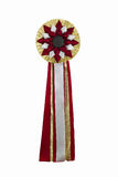 Gold ribbon. Award. Rosette of golden, red and silver satin fabric with a ribbon tail isolated on white Stock Photography