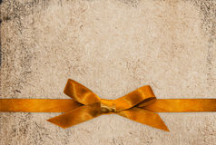 Gold ribbon bow on paper textured background Royalty Free Stock Image