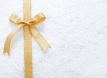 Gold ribbon and bow on snow. Decorative simple gold ribbon and bow on a background of winter snow with copyspace for your Christmas or festive greeting Royalty Free Stock Photography