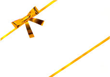 Gold ribbon with a bow on white Stock Photos