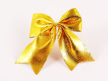 Gold  ribbon-knot. On white with shadows Stock Photography