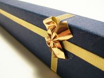 Gold ribbon over blue box - ornaments Royalty Free Stock Photography