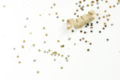 Gold ribbon with stars. A golden ribbon curled with sparkles of silver and gold stars on white background Royalty Free Stock Photo