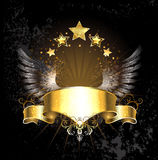 Gold ribbon with wings. Gold ribbon decoration angel wings and gold stars on a black background Royalty Free Stock Photography