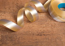 Gold ribbons on wooden background Royalty Free Stock Images